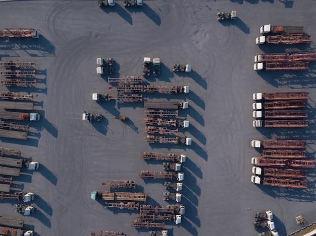 ロジスティックセンター、ビジネス貨物輸送インポートエクスポート輸送でトレーラートラックの読み込みの空撮。