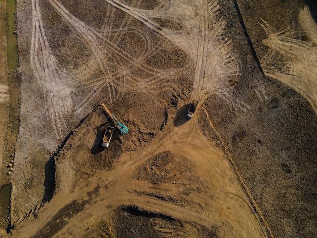 Вид с воздуха на грузовик и экскаватор или экскаватор с обратной лопатой, работающие на строительной площадке
