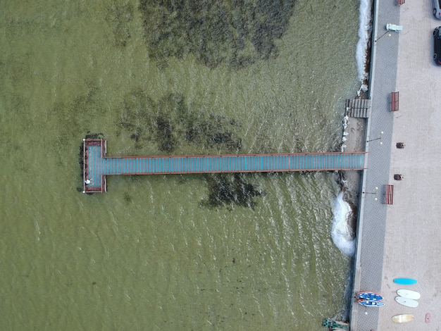 Аэрофотоснимок бирюзовой воды с деревянной пристани на озере