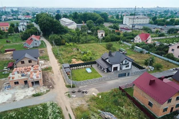 Вид с воздуха на недостроенный каркас строящегося частного дома в дачной зоне.