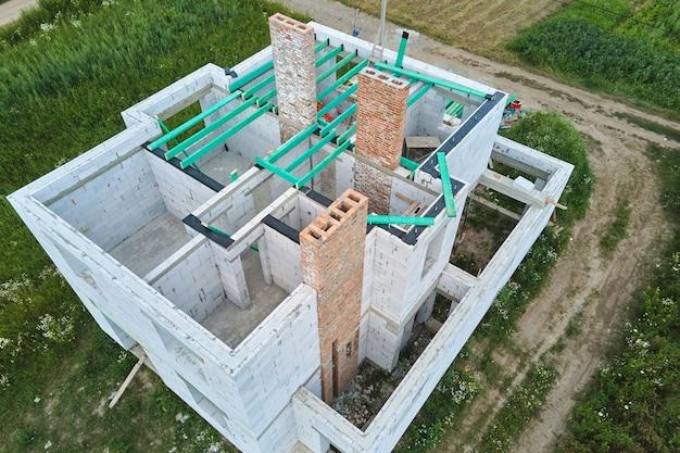 Вид с воздуха на незавершенный каркас частного дома со стенами из легкого газобетона и строящимися деревянными балками крыши.