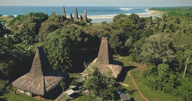 Вид с воздуха на уникальные дома индонезии с крышами на песчаном побережье бухты океана и на зеленых тропических джунглях. природное разнообразие зелени долины и райского песчаного пляжа острова сумба, азия