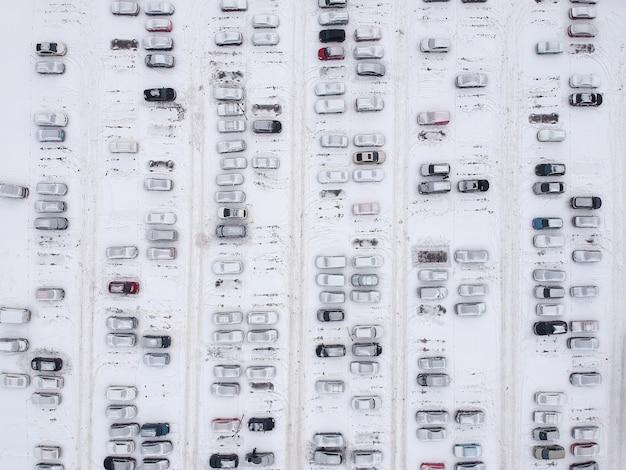 도시 주차장의 공중보기는 겨울에 신선한 눈으로 덮여 있습니다.
