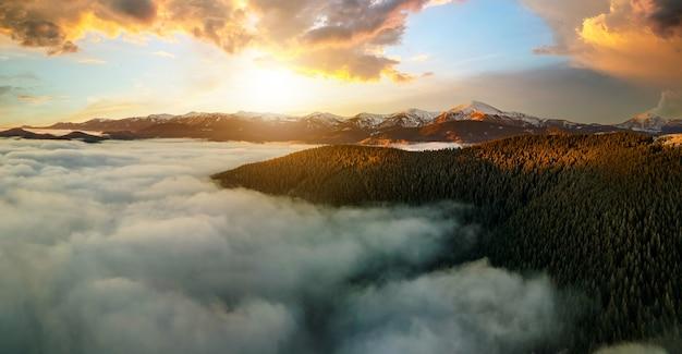 Вид с воздуха на яркий восход солнца над горными холмами карпат, покрытыми вечнозеленым еловым лесом осенью.