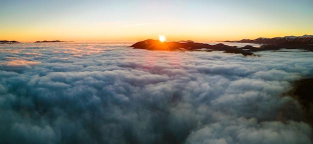 Вид с воздуха на яркий восход солнца над белыми плотными облаками с далекими темными горами на горизонте.