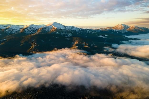 Вид с воздуха на яркий восход солнца над белым густым туманом с далекими темными карпатами на горизонте.