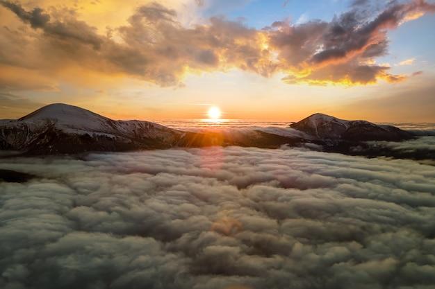 수평선에 먼 어두운 카르파티아 산맥이 있는 짙은 안개 위로 생생한 일출의 공중 전망.