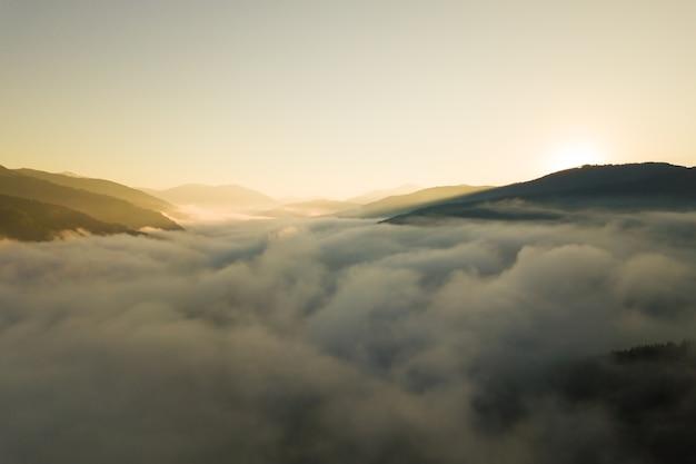 Вид с воздуха на яркий восход солнца над белым густым туманом с далекими темными силуэтами горных холмов на горизонте.