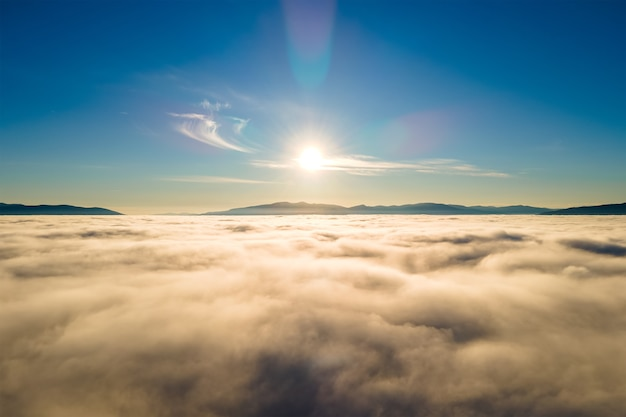 Вид с воздуха на яркий закат над белыми плотными облаками с далекими темными горами на горизонте.