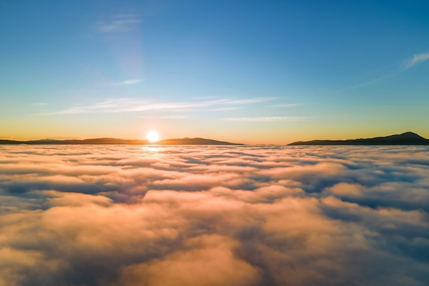 수평선에 먼 어두운 산과 흰색 짙은 구름 위에 활기찬 일몰의 공중 보기.