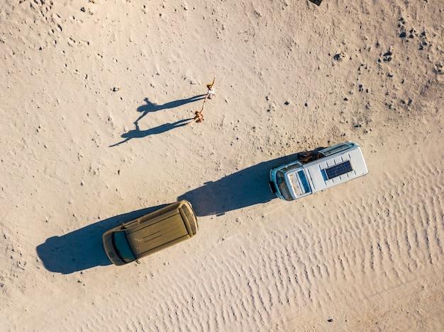 一緒に古いバンと一緒に旅行を楽しんでいる女性の放浪癖の人々のカップルの空撮