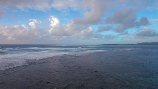 雲と青空と混ざらない海の喫水線の空撮モーリシャス島