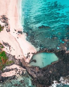 Вид с воздуха на волны, разбивающиеся о скалы