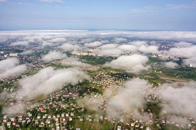 建物の行と夏の緑の野原の間の曲がりくねった通りの町または村の上の白い雲の空撮。上からの田園風景。