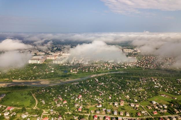 건물 또는 여름에 그린 필드 사이 매력적인 거리의 행 마을 또는 마을 위의 흰 구름의 공중 전망. 위에서 시골 풍경입니다.