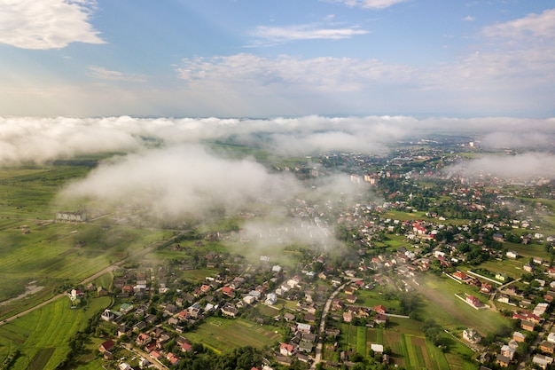 建物の行と夏の緑のフィールドの間の曲がりくねった道の町や村の上の白い雲の空撮。上からの田園風景。