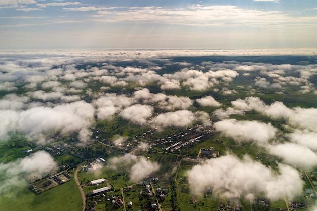 Вид с воздуха на белые облака над городом или деревней с рядами зданий и извилистыми улочками между зелеными полями летом.