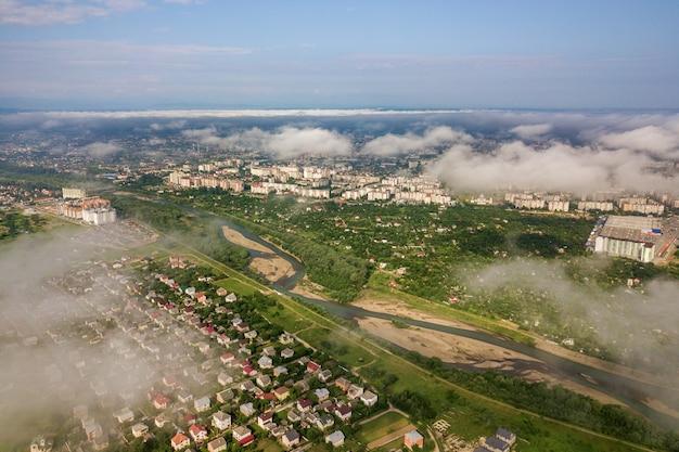 建物の行と夏の緑のフィールドの間の曲がりくねった通りの町の村の上空から見た白い雲。