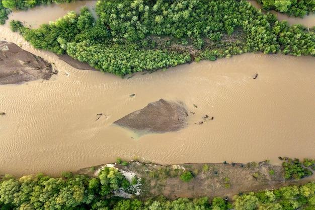 봄에 폭우 동안 홍수 기간에 진흙 투성이 물과 넓은 더러운 강의 공중보기.