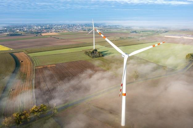 Вид с воздуха на ветряную турбину в тумане, окружающая среда, возобновляемые источники энергии, выработка электроэнергии, летний пейзаж, дрон