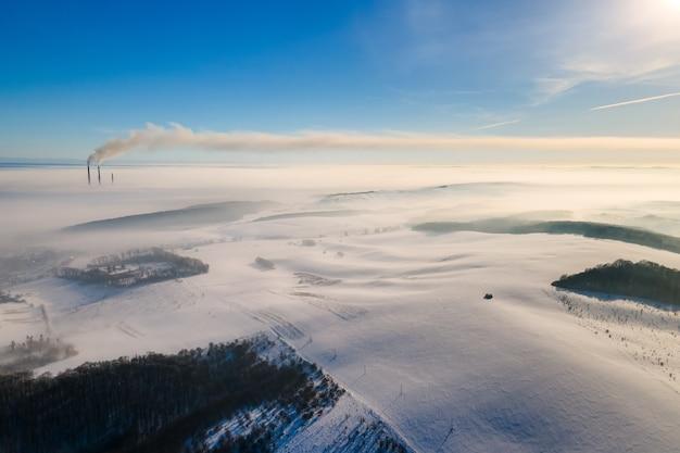 霧の田園地帯と黒い汚れた煙の汚染環境を放出する遠くの工場のパイプで冬の風景の空撮。