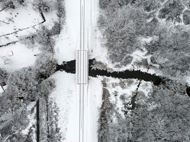 雪に覆われた川を横断する鉄道と冬の風景の空撮。ドローン写真。ロシアの冬の風景。上面図