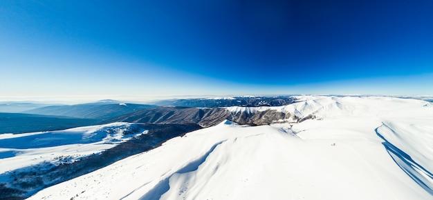 青い明るい空と晴れた冬の日に雪に覆われた山の素晴らしい波状の尾根と斜面の空撮