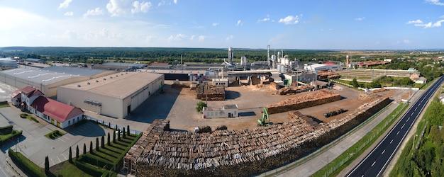 工場製造ヤードで木材のスタックを持つ木材加工工場の航空写真。