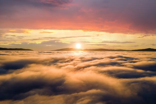 수평선에 먼 산들과 흰색 푹신한 구름 위에 노란색 일몰의 공중 전망.