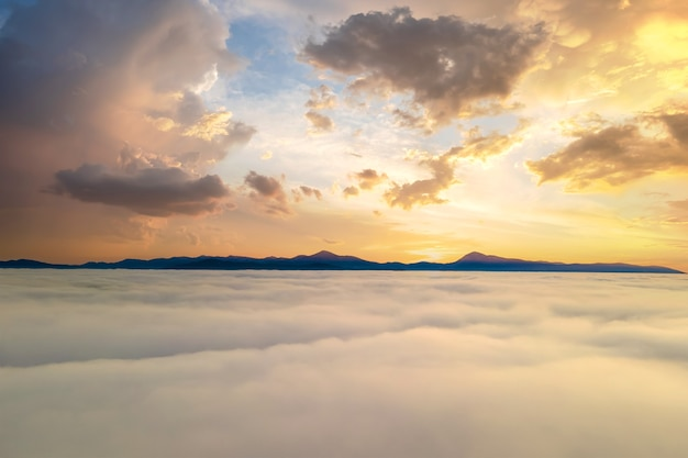 수평선에 먼 산과 흰 푹신한 구름 위에 노란색 일몰의 공중 전망.
