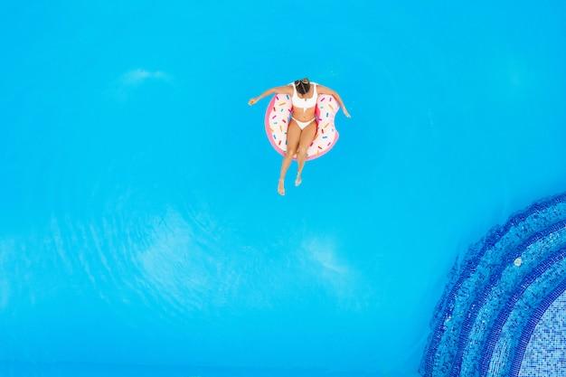 Вид с воздуха молодой красивой девушки в белом бикини ослабляя на раздувном донуте в бассейне. летние каникулы фон