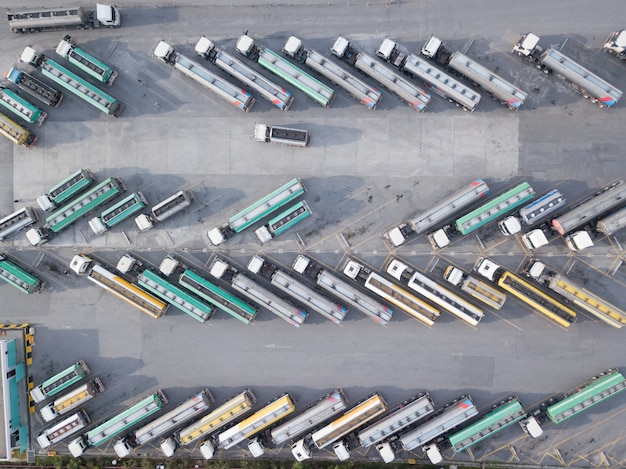 Aerial view of oil trucks are parked in the parking lot waiting to transport the oil.