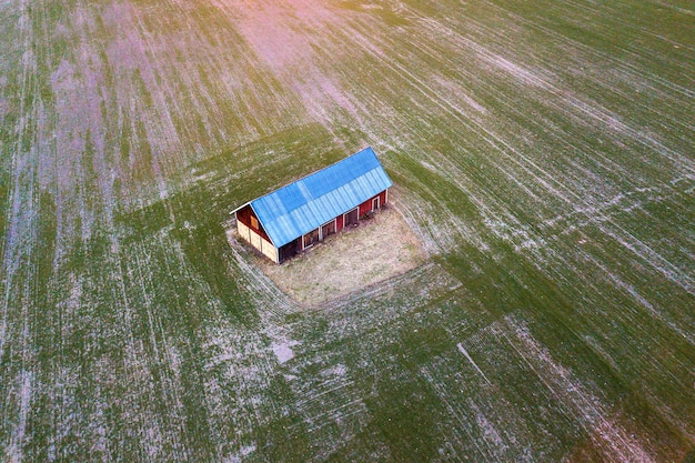 Aerial view of old wooden barn with bright roof in green field on sunny spring day. drone photography.