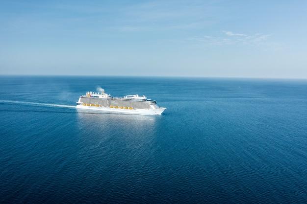 Вид с воздуха на огромный круизный лайнер плывет по бирюзовому морю