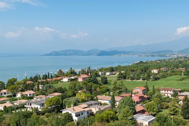 Вид с воздуха на прибрежной деревне в зеленой долине возле озера гарда