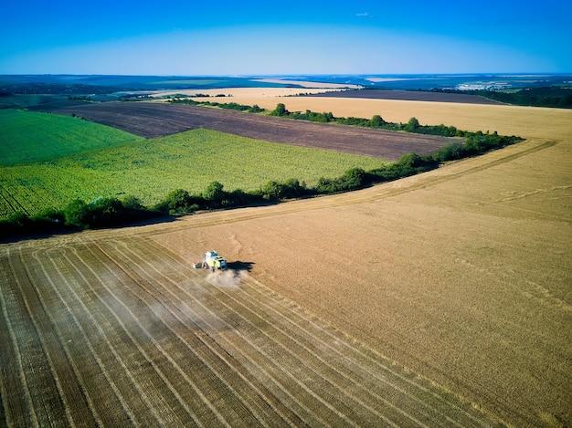 コンバインの空撮は日没時に小麦を集めます。穀物畑の収穫、収穫期。部分的に収穫された畑の収穫機の眺め。