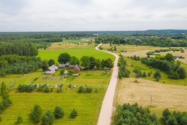 Вид с воздуха на сельскую сельскую дорогу через сельскохозяйственные угодья и деревню