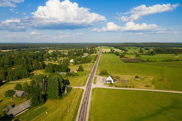 森林、農地、村を通る田舎の道路の空中写真