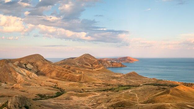 Вид с воздуха на тихую бухту и черное море. закат в коктебеле, крым