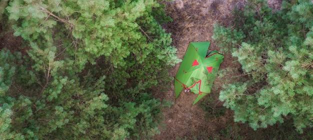 Вид с воздуха на палатку в лесу на концепции кемпинга
