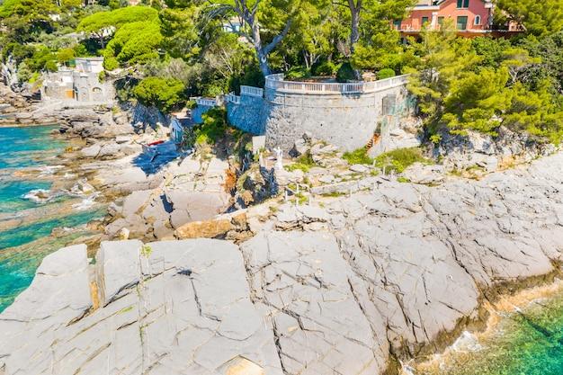 イタリア、ジェノヴァの近くのカモーリのリグリア海の岩の多い海岸に位置するカラフルな家が付いている都市の空撮。岩の多い海岸線は青緑色の水で洗われています。