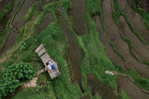 上部の航空写真。若い人たちの2人の恋人が木製の橋の上に横たわっています。ウブドのテガラランの棚田、バリ島を旅する幸せなカップル。インドネシアでの新婚旅行の夏の旅行。幸せな人々。
