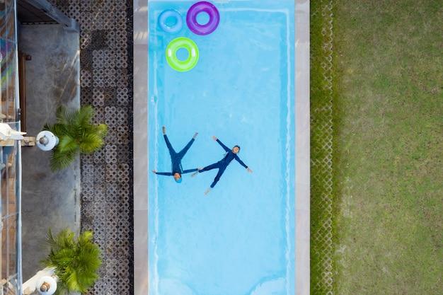 スイミングプールで泳いでいる子供の航空写真または平面図