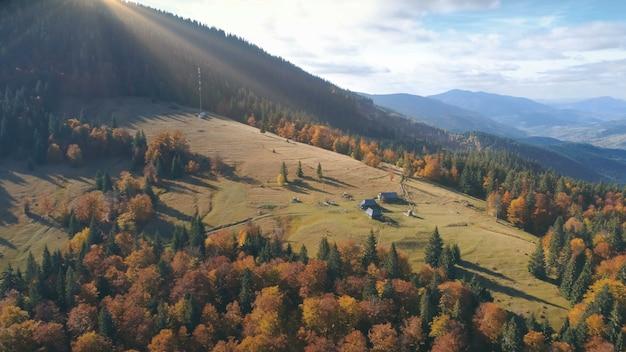 オレンジ色の中にロンリーの家と美しい秋の山の風景黄色の牧草地の空撮