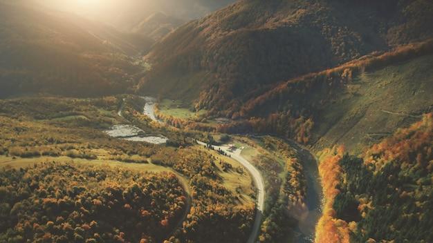 劇的な秋の山の風景の空撮。緑の牧草地、オレンジ色の丘、山川、夕焼け空を背景に松の木の森。カルパティア山脈、ウクライナ、ヨーロッパ。ヴィンテージレトロダークトーニングフィルター。