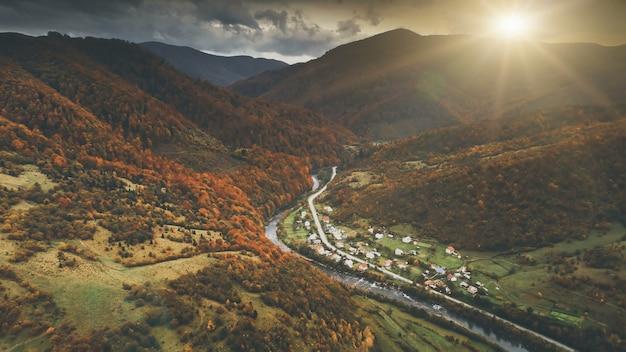 극적인 가을 일몰 풍경을 통해 공중 보기입니다. 협곡에 있는 작은 산악 마을은 초원, 오렌지색 언덕, 소나무 숲으로 둘러싸여 있습니다. carpathians, 우크라이나, 유럽. 빈티지 레트로 다크 토닝 필터.