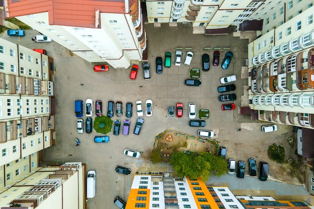 Aerial view of parked cars on parking lot between high apartment buildings
