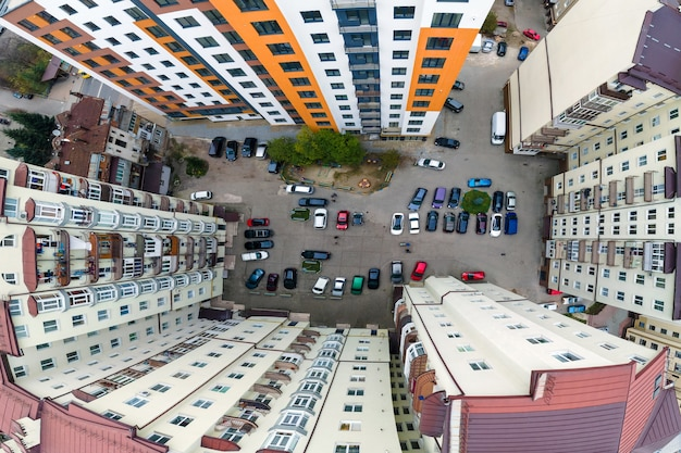 Aerial view of parked cars on parking lot between high apartment buildings.