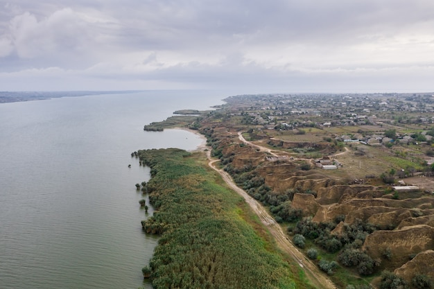 Aerial view of a path along huge lake with beautiful sand dunes and green shore