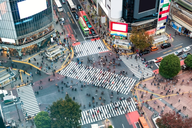 Aerial view of pedestrians walking across with crowded traffic at shibuya crossing square